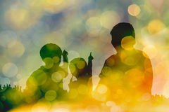 Silhouette of mother and two kids on bokeh abstract in yellow ba Royalty Free Stock Photo
