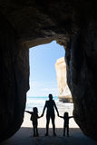 Silhouette of mother with two kids in a cave at Tunnel beach Stock Photo