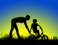 Silhouette of a mother who teaches his son to ride a bike Stock Photo