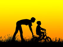 Silhouette of a mother who teaches his son to ride a bike Royalty Free Stock Images