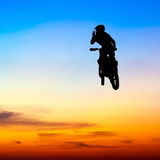 Silhouette of motocross rider jump in the sky Stock Photos