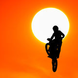 Silhouette of motocross rider jump in the sky Stock Images