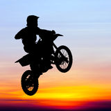 Silhouette of motocross rider jump in the sky Stock Photo
