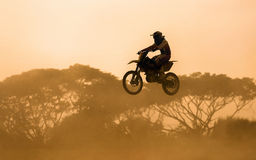 Silhouette of motocross rider jumping Stock Photos