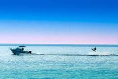 Silhouette of motor boat and wakeboarder jumping Stock Photos