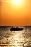 Silhouette of a motor speed boat at sunset Royalty Free Stock Images