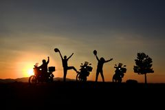 Motorcycle travel and team success. Silhouette of motorbikes and riders on a hilltop at sunset waving their arms in jubilation stock photography
