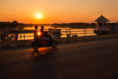 Silhouette of motorcycle on the water dam at sunset. Royalty Free Stock Image