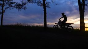 The silhouette of a motorcyclist on a background of nature, who rides the forest part on a cross or utilitarian. The silhouette of a motorcyclist in a protective stock video footage