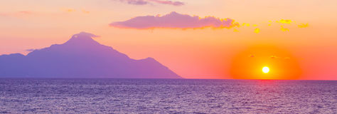 Silhouette of mount Athos at sunrise or sunset with light rays and sea panorama. Banner background with silhouette of mount Athos at sunrise or sunset with light stock photo