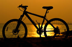 Silhouette mountain bicycle on sunset background. Silhouette mountain bicycle on sea sunset background Stock Photography