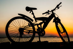 Silhouette of mountain bike parking on jetty beside sea with sun Stock Photos