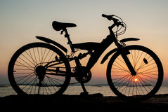 Silhouette of mountain bike parking beside sea with sun Stock Photos