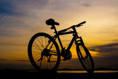 Silhouette of mountain bike parking beside sea with sun Royalty Free Stock Image