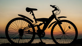 Silhouette of mountain bike parking beside sea with sun Stock Image