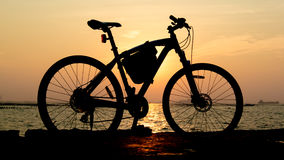 Silhouette of mountain bike at sea with sunset sky Royalty Free Stock Photography