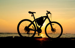 Silhouette of mountain bike at sea with sunset sky Royalty Free Stock Image
