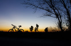 Silhouette of Mountain bike at sunset on blue sky Stock Photos