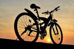 Silhouette of mountain bike with sunset Stock Photos
