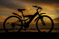 Silhouette of mountain bike with sunset sky beside sea Royalty Free Stock Image