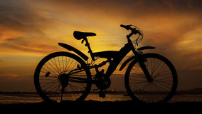 Silhouette of mountain bike with sunset sky beside sea Stock Photo