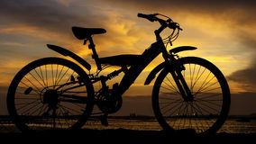 Silhouette of mountain bike with sunset sky beside sea Royalty Free Stock Images