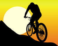 Silhouette of a mountain  biker. In the sun and the orange sky Royalty Free Stock Photography