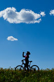 Silhouette of mountain biker drinking. Royalty Free Stock Images