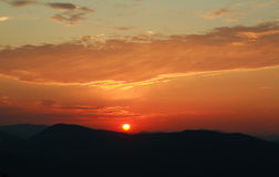 Silhouette of the mountain hills against setting sun Stock Photo