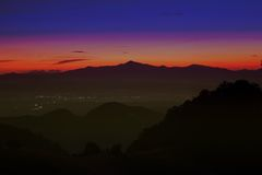 Silhouette of mountain. Silhouette of mountain with light from sunset and city Royalty Free Stock Photography