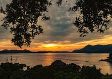 Silhouette of Mountain Near Body of Water during Sunset Royalty Free Stock Image