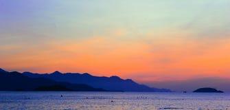 Silhouette of Mountain Beside Ocean during Orange Sunset Stock Image