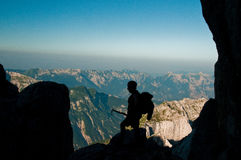 Silhouette of a mountaineer. Silhoueeter of a mountaineer with an ice axe in his hands stock photography