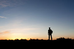 Silhouette of a mountaineer. Enjoying the sunset view from the summit of a mountain stock photo