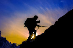 Silhouette of mountaineer and sunset. Stock Photo