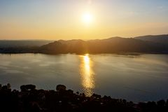 Silhouette of the mountains and the town of Arona in Italy at sunset and water. View from above Stock Images