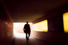 Silhouette in movement of a human figure walking through a tunnel stock image
