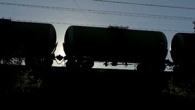Silhouette of a moving freight train with tanks against the bright sun stock video footage