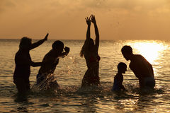Silhouette Of Multi Generation Family Having Fun In Sea Stock Photo