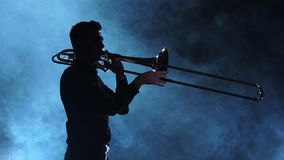 Silhouette musician man playing on trombone. Smoky studio, slow motion stock video footage