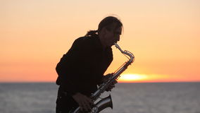 The silhouette of a musician playing saxophone on stock video