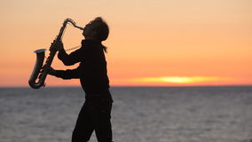 The silhouette of a musician playing saxophone on stock video footage