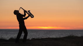 The silhouette of a musician playing saxophone on stock footage