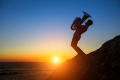 Silhouette of musician with Tuba on rocky sea coast . Stock Photography