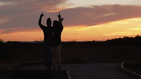 Silhouette of musicians singing and dancing. Man and woman sing and dance raising hands up outdoors on a sunset sky background stock video footage