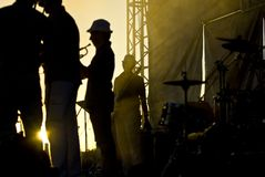 Silhouette of musicians at the stage. Silhouette of few musicians, staying at stage royalty free stock photo