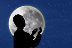 Silhouette of muslim man praying under blue moon Stock Images