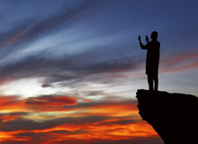 Silhouette of muslim man standing on the top of cliff Royalty Free Stock Photography