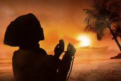 Silhouette of muslim woman praying. On the beach Stock Photography