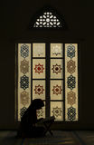 Silhouette Muslim woman reading Koran in the evening at Mosque Royalty Free Stock Images